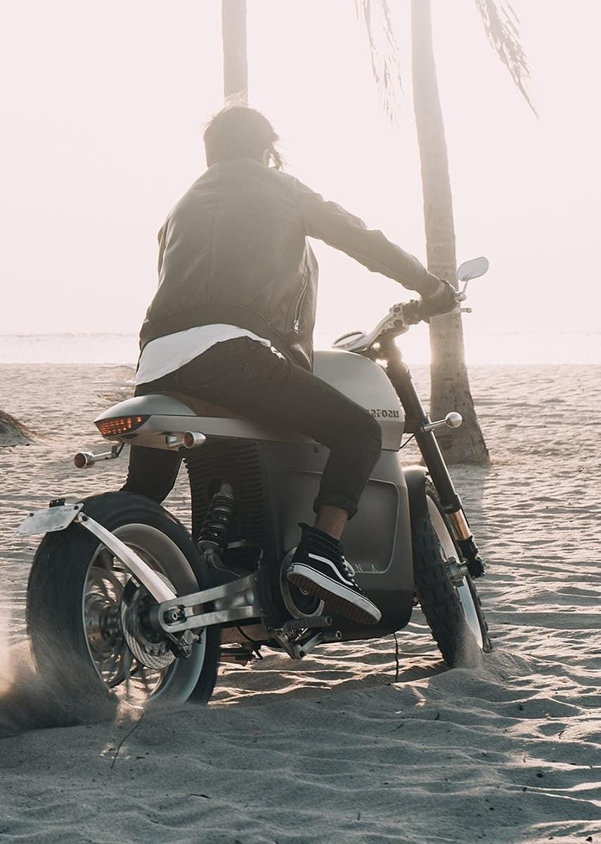 tarform scrambler electric motorcycle on beach.